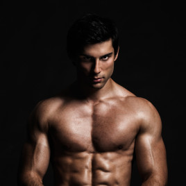 A handsome male model posing at a studio in front of a black background.