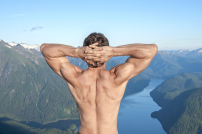 Back of shirtless muscular Caucasian man stretching arms with fingers locked behind head as he enjoys the magnificent scenic view over body of water surrounded by snow capped mountains near Sitka, Alaska