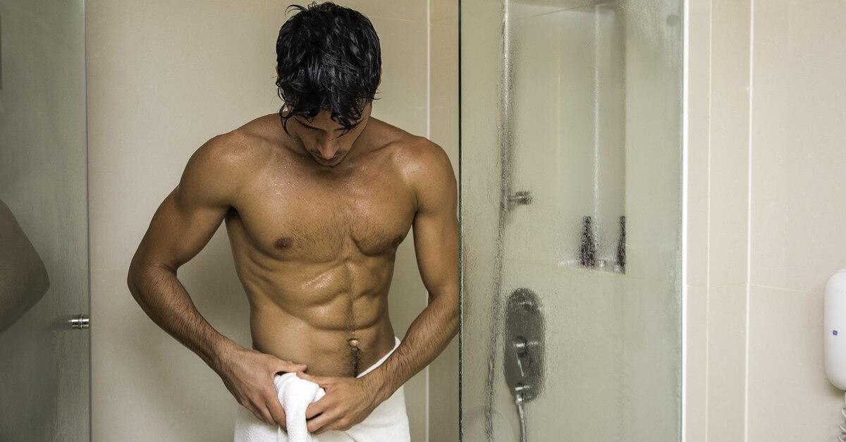 Młody chłopak pod prysznicem z ręcznikiem