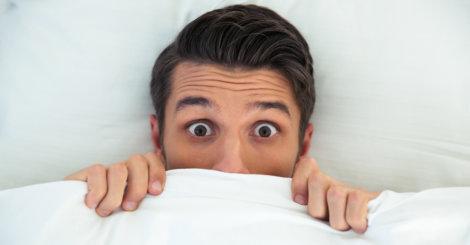 Zdziwiony chłopak w łóżku