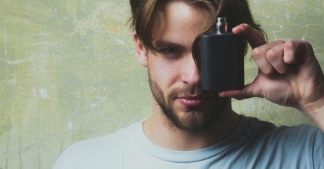 Mężczyzna trzyma perfumy w dłoni