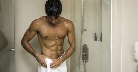 Młody chłopak wychodzi spod prysznica z ręcznikiem
