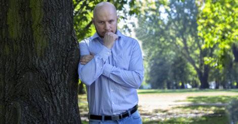 Tomasz Saweczko w koszuli, jeansach i pasku w parku
