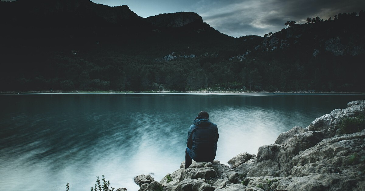 Mężczyzna nad jeziorem, melancholia i smutek