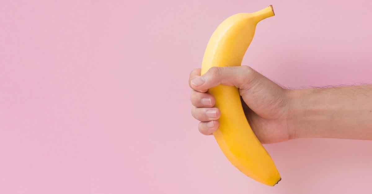Mężczyzna trzyma banana w dłoni