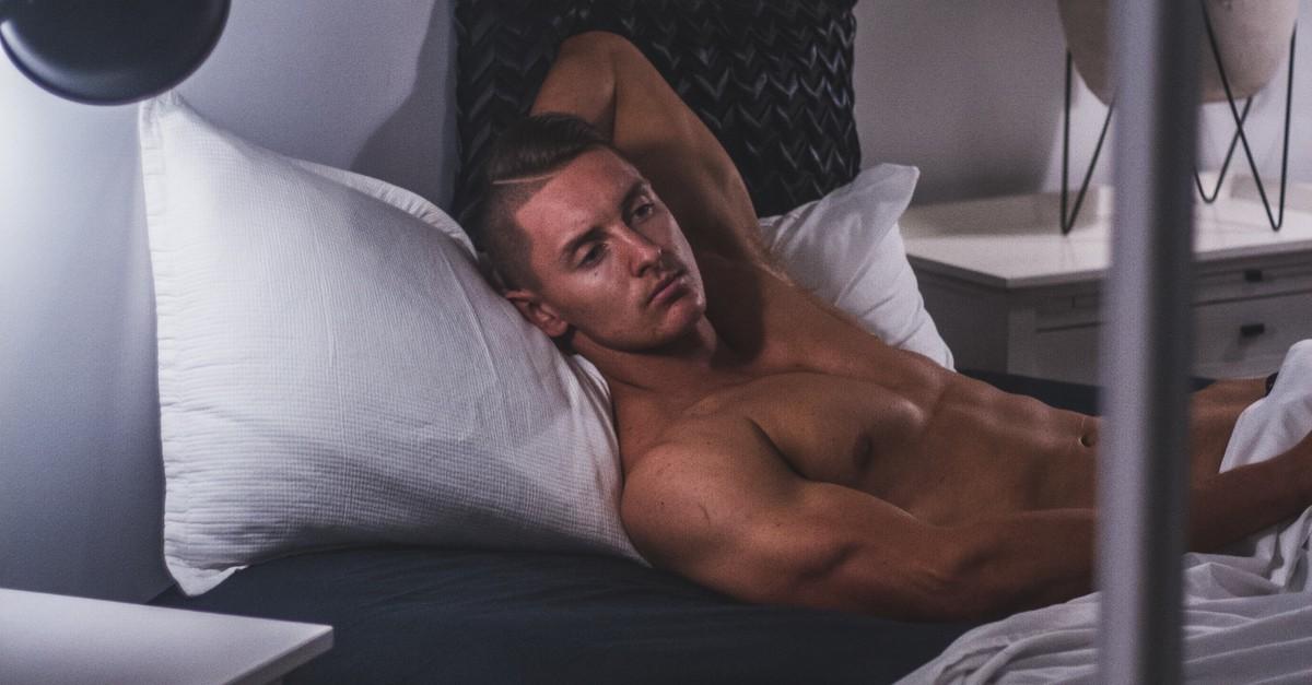 Mężczyzna bez koszulki leży na łóżku