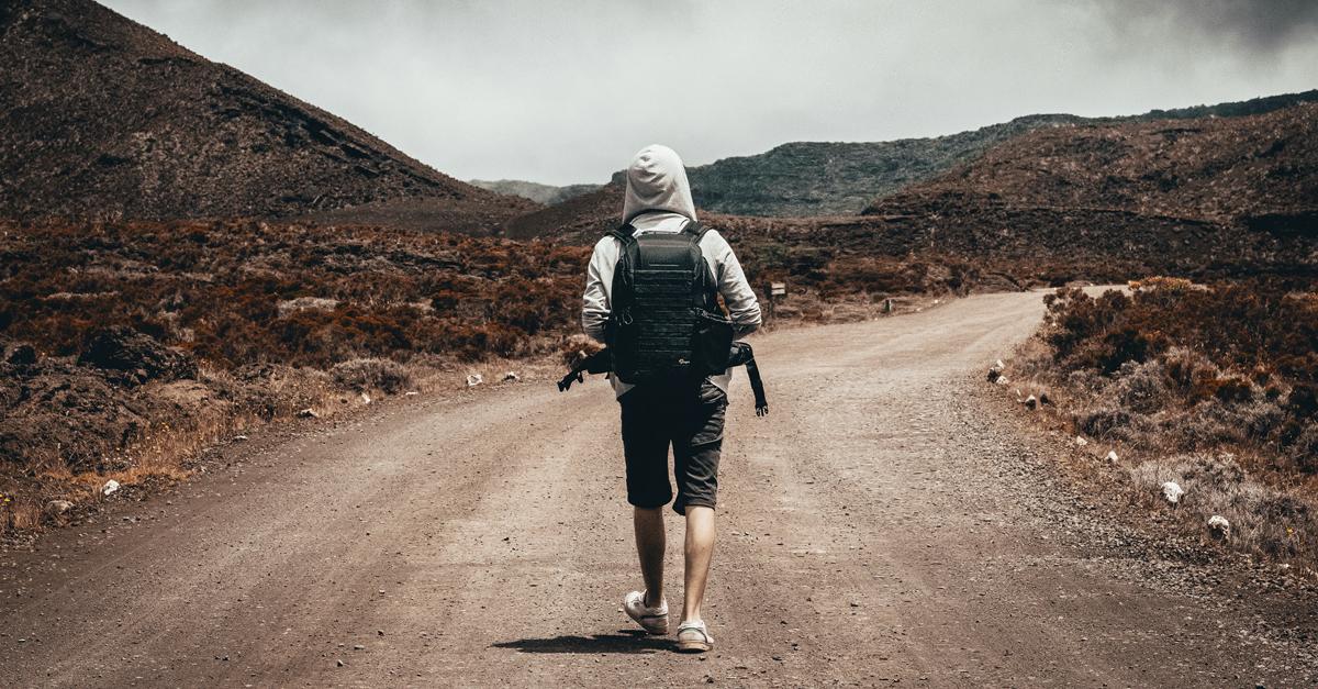 Mężczyzna idący polną drogą w górach
