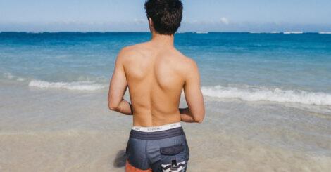 Młody facet na plaży w szortach analog