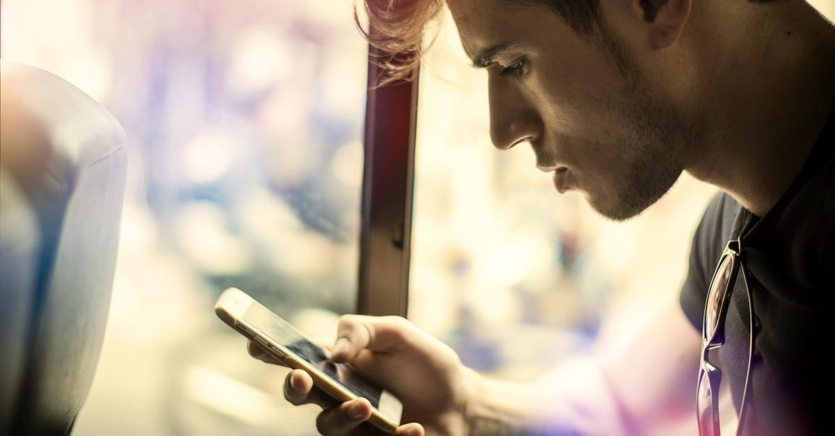 Młody mężczyzna patrzy w telefon komórkowy trzymany w dłoni