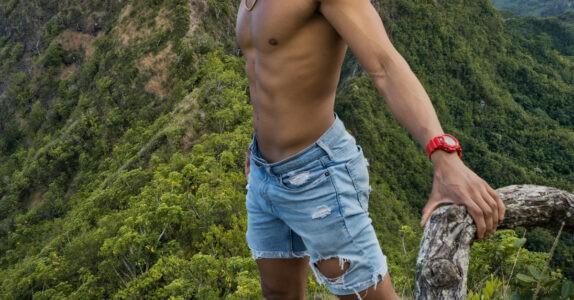 Młody chłopak bez koszulki w górach porośniętych drzewami